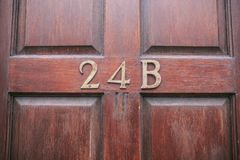 Номер адреса в деревянной двери стоковое фото rf