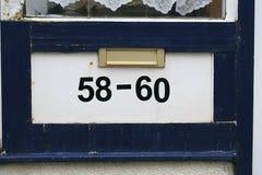 Номер адреса в деревянной двери стоковые изображения rf
