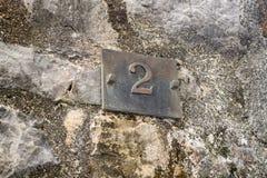 Номер два дома на старой каменной стене стоковые фотографии rf