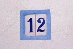 Номер дома на керамических плитках на белой стене стоковые фотографии rf