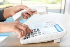 Номер женщины набирая на телефоне на таблице стоковые изображения