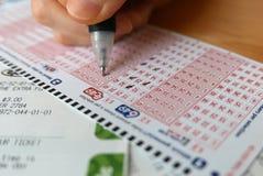 Номер маркировки руки женщины на билете лотереи 649 Стоковые Фото