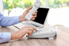 Номер молодого человека набирая на телефоне на рабочем месте стоковые изображения rf