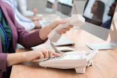 Номер оператора службы технической поддержки набирая на телефоне на таблице стоковая фотография rf