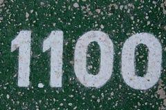 Номер покрашен на белизне на грубой земле на зеленой предпосылке Стоковое фото RF