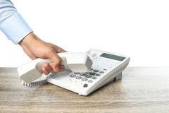 Номер человека набирая на телефоне на таблице стоковое изображение