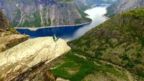 Норвегия девушка на краю утеса Trolltunga Антенна соперничает видеоматериал