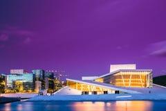 Норвегия Осло Взгляд вечера ночи загоренного норвежского национального дома оперы и балета среди современного высотного здания Стоковые Фото