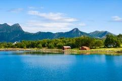 Норвежское побережье, типичный ландшафт на норвежской береговой линии с горами внутри подпирает и малые красные дома на береге Стоковое Изображение RF