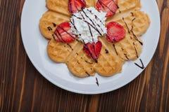 Норвежское сердце сформировало waffles покрытые с клубниками, мятой и взбило сливк на белой плите и деревянной предпосылке Стоковые Фотографии RF