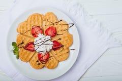 Норвежское сердце сформировало waffles покрытые с клубниками, мятой и взбило сливк на белой плите и белой деревянной предпосылке Стоковые Изображения