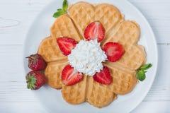 Норвежское сердце сформировало waffles покрытые с клубниками, мятой и взбило сливк на белой плите и белой деревянной предпосылке Стоковое Изображение