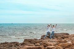 Нормальные девушки на пляже с их оружиями вверх Стоковые Изображения