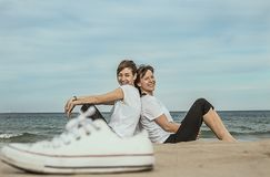Нормальные женщины на пляже усмехаясь и сидя на песке Стоковое Фото