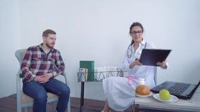 Нормированность веса, женщина диетврача доктора делает измеренияя с измеряя лентой к терпеливому мужчине и рекомендует акции видеоматериалы
