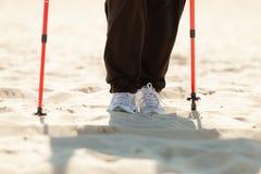 Нордический гулять Женские ноги на пляже Стоковые Фотографии RF