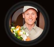 Носильщик мелких грузов при цветки увиденные через телезрителя двери стоковая фотография rf