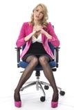 Носить бизнес-леди думая розовый и сидеть в стуле офиса стоковые фотографии rf
