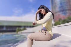 Носить молодой женщины вскользь смотрящ ее вахту пока сидящ стоковые фото