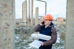 Носка работника человека оранжевый шлем с строительной площадкой Стоковые Изображения