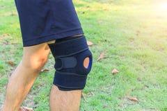 Носка человека Patella расчалки поддержки колена с солнечным светом в парке стоковые изображения