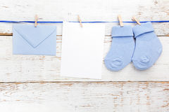 Носки малого мальчика голубые, пустая карточка и evelop на белой деревянной предпосылке Плоское положение Стоковое фото RF