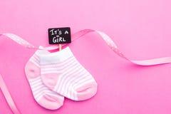 Носки ребёнка - розовые и белые с лентой на розовой предпосылке с ей ` s знак классн классного девушки Стоковое Фото
