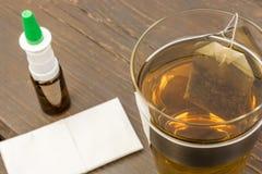 Носовой платок, носовые брызги и травяной чай на деревянном столе как помощь с холодами стоковая фотография