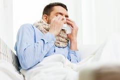 Нос больного человека дуя с бумажной салфеткой дома Стоковые Фотографии RF