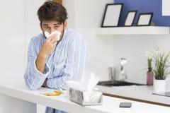 Нос молодого больного человека дуя в салфетке стоковое изображение