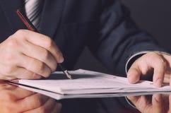 Нотариус подписывая контракт с авторучкой в концепции темной комнаты Стоковые Изображения RF
