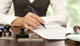 Нотариус подписывает документы в офисе стоковое фото rf