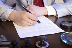 Нотариус подписывает документы от нашего офиса стоковые фото