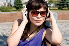 Нот девушки слушая в наушниках Стоковая Фотография