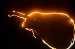 нот иллюстрации электрической гитары принципиальной схемы Акустическая гитара на темной предпосылке под луч светом с дымом с косм Стоковые Изображения RF