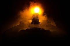 нот иллюстрации электрической гитары принципиальной схемы Акустическая гитара на темной предпосылке под луч светом с дымом с косм Стоковое Изображение RF