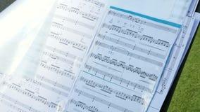 Нот листа Мелодия покрывает на стойке, конце вверх Музыкальные примечания с селективным фокусом видеоматериал