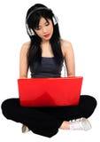 Нот молодой азиатской женщины слушая от compute Стоковые Изображения
