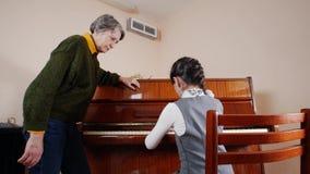 нот урока Девушка играя рояль, старшие стойки учителя около рояля и помощь с игрой Взгляд слайдера игры видеоматериал