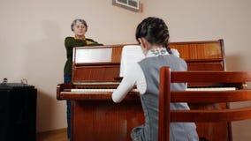 нот урока Девушка играя рояль, старшие стойки учителя около рояля Взгляд слайдера игры от задней части девушки сток-видео
