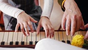 нот урока Девушка играя рояль, старший учитель сидит около ее и помощи с игрой взгляд сверху акции видеоматериалы