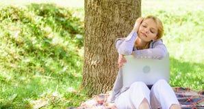 Ноутбук девушки мечтая в парке сидит на траве Мечта об успешном проекте Женщина мечтательная с работой ноутбука outdoors стоковое изображение rf