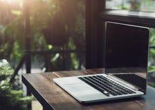 Ноутбук показывая пустой экран в ресторане кофейни, удобном месте службы, конце-вверх удобного места службы в офисе стоковая фотография