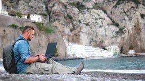 Ноутбук пользы человека, тетрадь, взгляд на смартфоне, получает звонок, находит информация на перемещении к стране foregin, сообщ видеоматериал