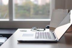 Ноутбук тетради в таблице стола в окнах и виде на город офиса W стоковое фото