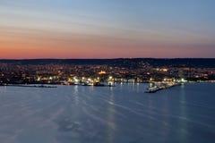 Ноча освещает от города и морского порта в Варне, Болгарии на сумерк с красивыми striped небом и водой Стоковая Фотография RF