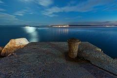 Ноча сняла старого пала на пристани с дистантным городком острова Стоковые Изображения