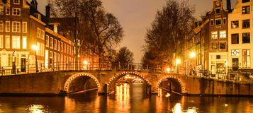 ноча amsterdam Загоренный мост над каналом воды, gracht Нидерланды Стоковые Фото