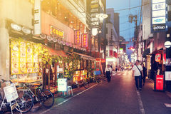Ночная жизнь на улице города Осака вместе с магазинами, барами, и ресторанами украшенными с неоновыми вывесками на ноче Стоковые Изображения RF