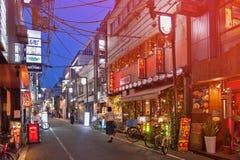 Ночная жизнь на улице города Осака вместе с магазинами, барами, и ресторанами украшенными с неоновыми вывесками на ноче Стоковая Фотография